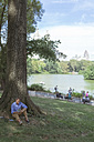 USA, Manhattan, Central Park, man with notebook sitting on a meadow in a park - BOYF00765