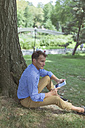 Man with mini tablet sitting on a meadow in a park - BOYF00771