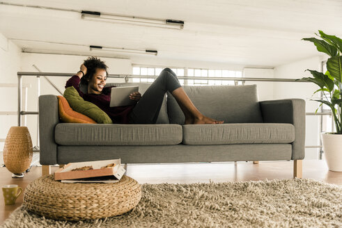 Smiling young woman lying on couch using tablet - UUF10313