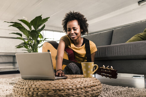 Smiling young woman at home with guitar and laptop - UUF10322
