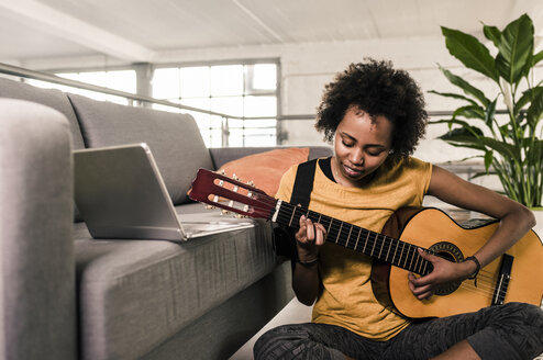 Young woman at home with laptop playing guitar - UUF10325