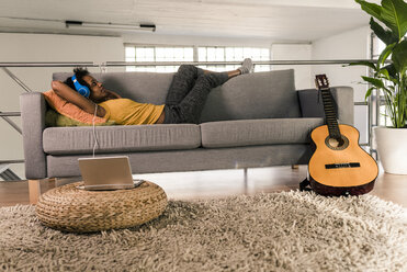 Young woman lying on couch with headphones connected to laptop - UUF10328