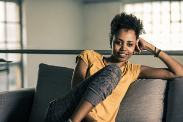 Portrait of smiling young woman sitting on couch - UUF10331