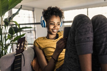 Smiling young woman on couch with headphones using tablet - UUF10334