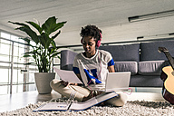 Young woman at home with headphones, laptop and documents next to guitar - UUF10340