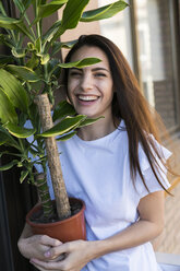 Portrait of laughing woman with Yucca in flowerpot - KKAF00660