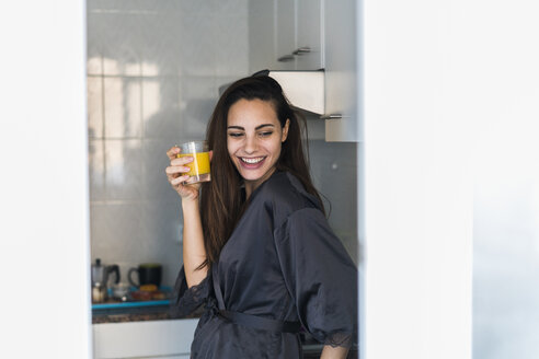 Portrait of laughing young woman with glass of orange juice in the kitchen - KKAF00669