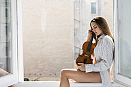 Young woman with eyes closed sitting on window sill holding violin - KKAF00678