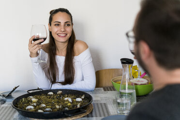 Portrait of smiling woman with glass of red wine sitting at laid table looking at her boyfriend - KKAF00690