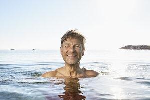 Portrait of happy man bathing in the sea - PDF01086