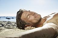 Portrait of man relaxing on sandy beach - PDF01089