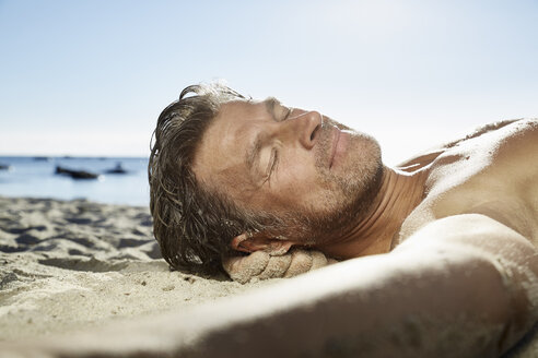 Portrait of man relaxing on sandy beach - PDF01089