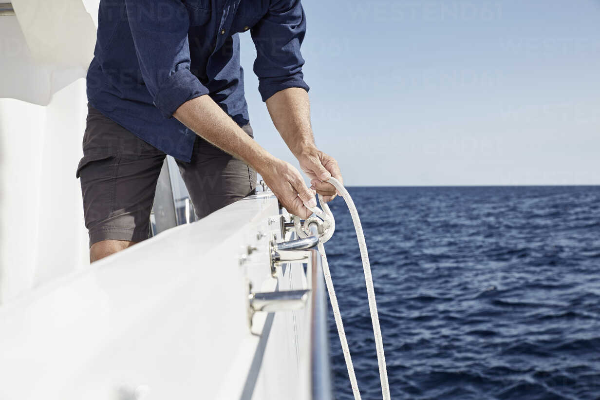 Man on motor yacht tying a knot, partial view - PDF01101 - Philipp Dimitri/Westend61
