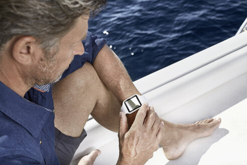 Man sitting on motor yacht looking at his smartwatch - PDF01104