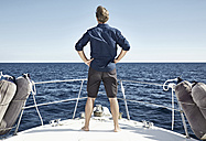Back view of mature man standing on his motor yacht with hands on hips - PDF01113