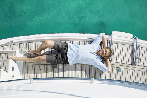 Smiling man lying on deck of his motor yacht - PDF01116