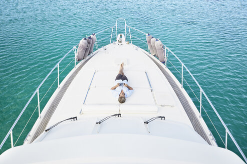 Smiling man lying on deck of his motor yacht using tablet - PDF01119