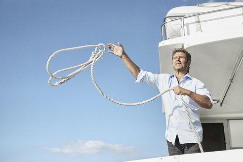 Mature man on motor yacht throwing rope - PDF01122