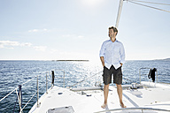 Mature man standing on sailing boat - PDF01131