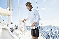 Mature man with rope on his sailing boat - PDF01134