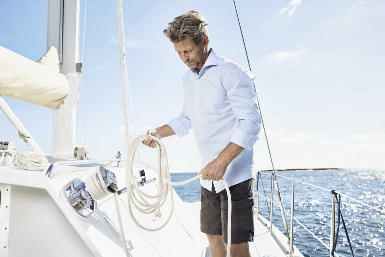 Mature man with rope on his sailing boat - PDF01134 - Philipp Dimitri/Westend61