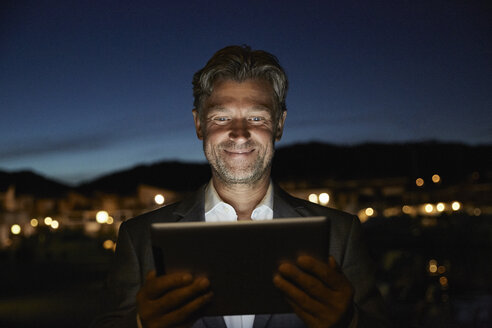 Portrait of smiling mature man standing looking at tablet in the night - PDF01149