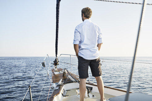Back view of mature man standing on his sailing boat looking at distance - PDF01155