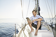 Smiling mature man sitting on his sailing boat using tablet - PDF01158