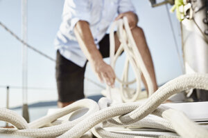 Rope on sailing boat with man working in the background - PDF01170