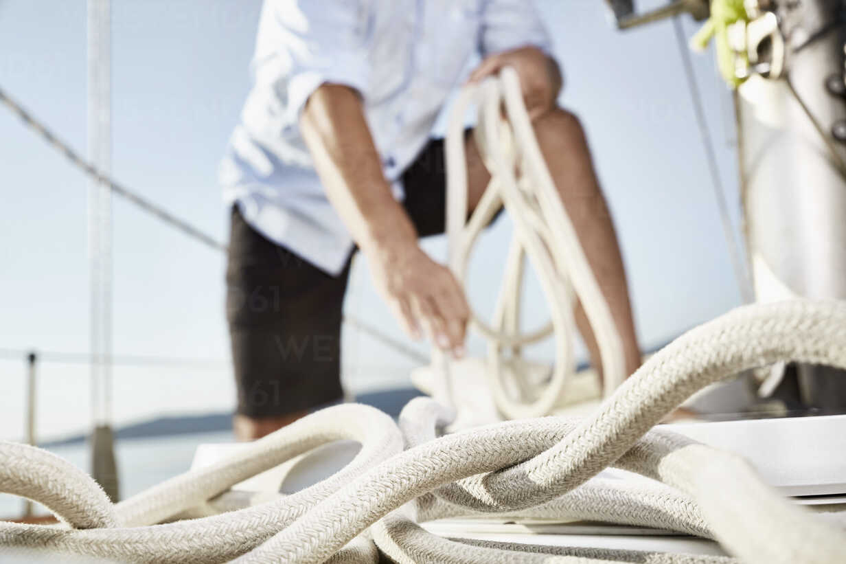 Rope on sailing boat with man working in the background - PDF01170 - Philipp Dimitri/Westend61