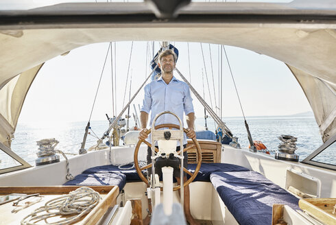 Mature man at helm of his sailing boat - PDF01176