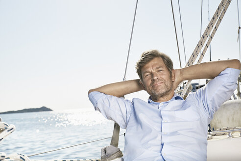 Portrait of smiling mature man relaxing on his sailing boat - PDF01182