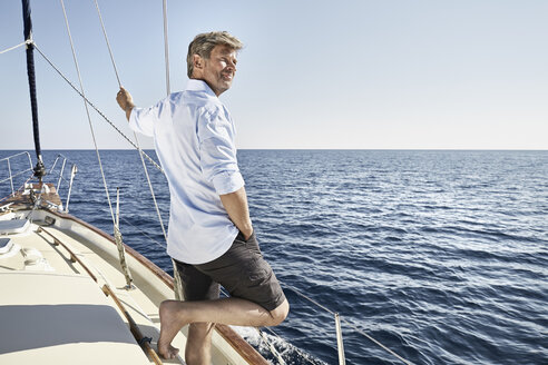 Smiling mature man standing on his sailing boat looking at distance - PDF01185