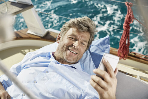 Portrait of smiling mature man lying on deck of his sailing boat looking at cell phone - PDF01191
