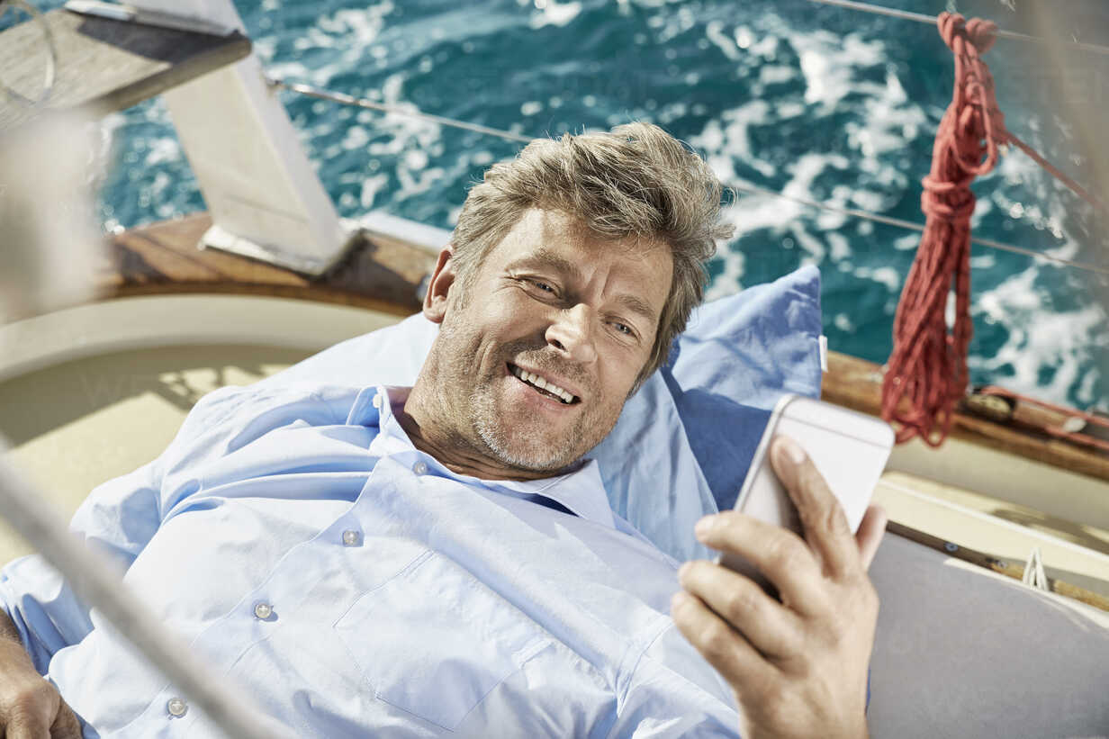 Portrait of smiling mature man lying on deck of his sailing boat looking at cell phone - PDF01191 - Philipp Dimitri/Westend61