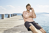 Smiling man on the phone sitting on jetty - PDF01197