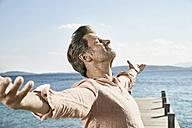 Man on jetty enjoying sunlight - PDF01200