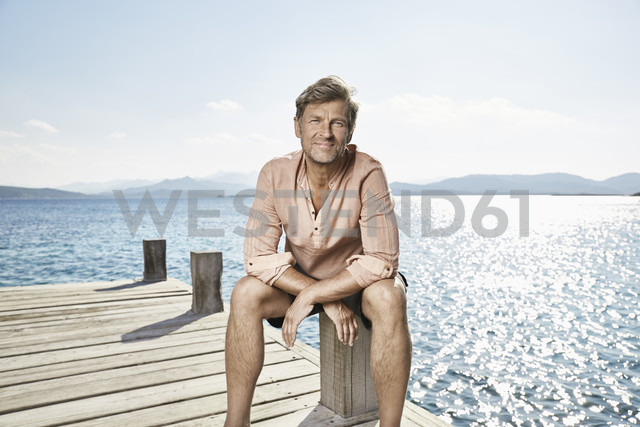 Portrait of smiling man sitting on jetty - PDF01206 - Philipp Dimitri/Westend61