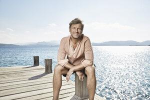 Portrait of smiling man sitting on jetty - PDF01206