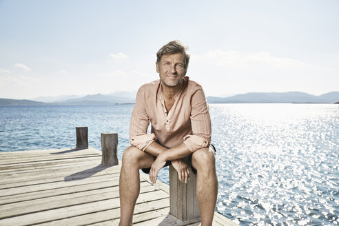 Portrait of smiling man sitting on jetty - PDF01206