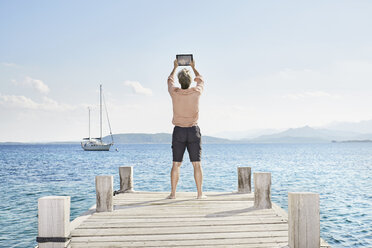 Back view of man standing on jetty taking selfie with tablet - PDF01209