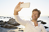 Portrait of smiling man taking selfie on the beach with cell phone - PDF01221