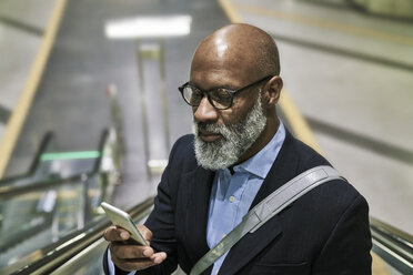 Businessman with smartphone reading messages on escalator - FMKF03786