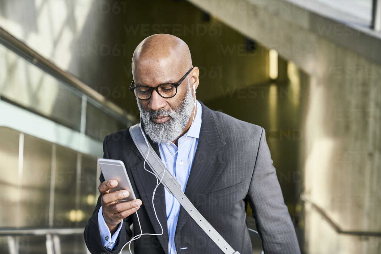 Businessman with smartphone reading messages on escalator - FMKF03789 - Jo Kirchherr/Westend61