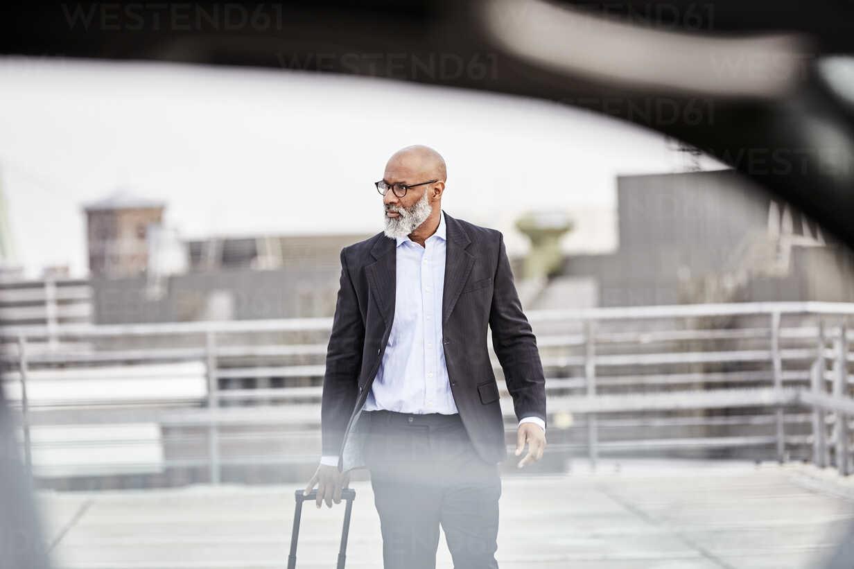 Businessman with trolley bag walking to his car - FMKF03798 - Jo Kirchherr/Westend61