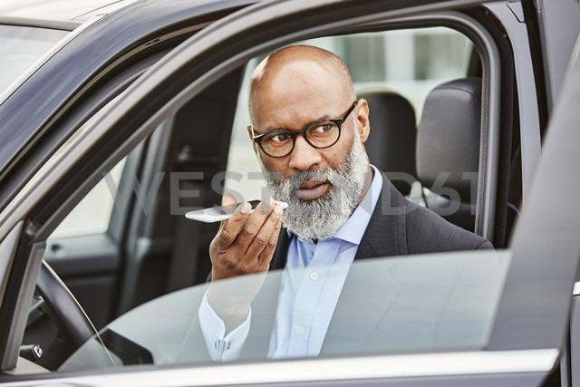 Businessman sitting in car using smartphone - FMKF03801 - Jo Kirchherr/Westend61