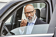 Businessman sitting in car using smartphone - FMKF03801
