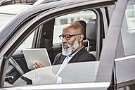 Businessman sitting in car using digital tablet - FMKF03804