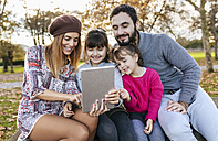 Family sitting on bench in autumnal park taking selfie with tablet - MGOF03185