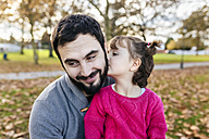 Little girl kissing her happy father in autumnal park - MGOF03188